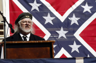 Mike Webb, a Sons of Confederate Veterans officer, stands before an oversized Mississippi state flag and speaks about the importance of keeping the Confederate battle emblem on the flag, at a rally with other pro flag groups at the state Capitol in Jackson, Miss., Tuesday, Jan. 19, 2016. (AP Photo/Rogelio V. Solis)
