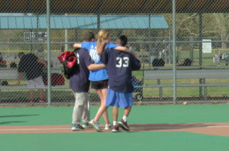 Miracle League volunteer congratulates players on a win.